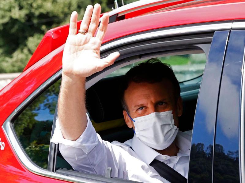 Emmanuel Macron gibt sich die Ehre: Der Präsident von Frankreich winkt auf der 18. Etappe aus einem Auto. Foto: Thomas Samson/AFP/dpa