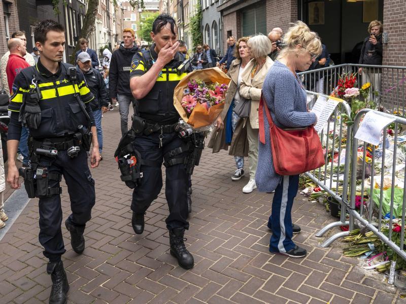 Polizisten bringen einen Blumenstrauß zu dem Blumenmeer für den Reporter Peter R. de Vries in der Leidswarsstraat. Foto: Evert Elzinga/ANP/dpa