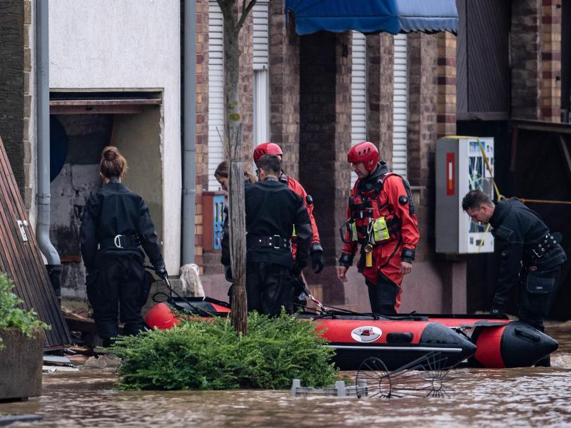 Rettungsschwimmer und Polizeitaucher bergen Menschen mit einem Schlauchboot in Erftstadt. Foto: Marius Becker/dpa