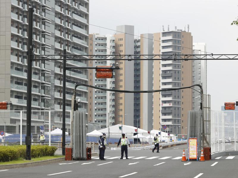 Sicherheitskräfte stehen vor dem Olympischen Dorf in Tokio. Foto: ---/Kyodo/dpa