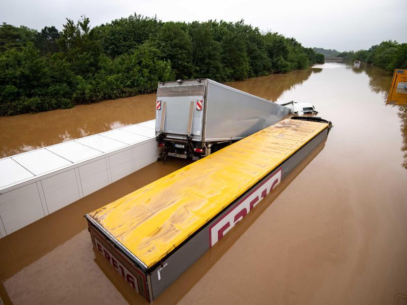 Drei Lastwagen stehen auf der überfluteten Bundesstraße 265 im tiefen Wasser und sind kaum mehr zu erkennen. Foto: Marius Becker/dpa