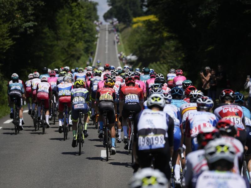 Mit großem Rückstand auf den Tagessieger: Das Fahrerfeld bei der 19. Etappe in Aktion. Foto: Daniel Cole/AP/dpa