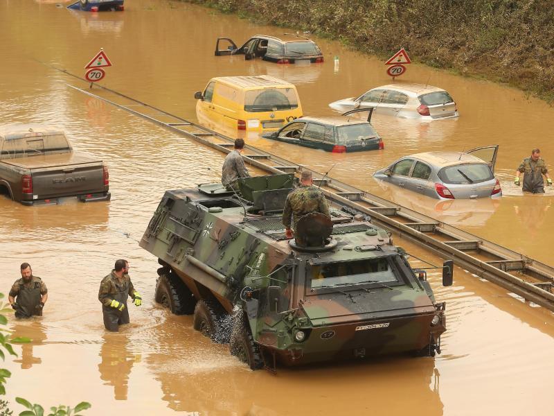 Die Bundeswehr untersucht in Erftstadt in NRW Fahrzeuge, die auf einer Bundesstraße von den Wassermassen überrascht worden waren - befürchtet wird, dass in den Autos und Lkw Tote liegen könnten. Foto: David Young/dpa