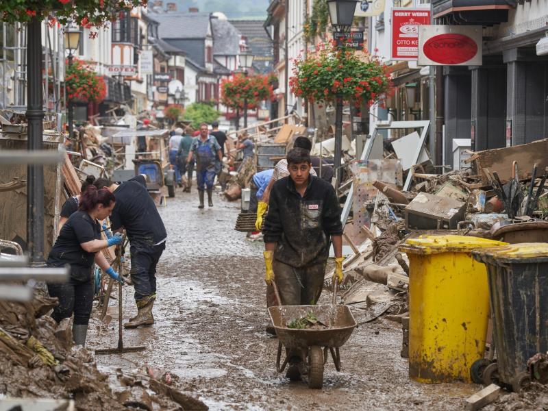 Kampf gegen die braunen Massen: In Ahrweiler versuchen Anwohner und Ladeninhaber, ihre Häuser von Schlamm zu befreien. Foto: Thomas Frey/dpa