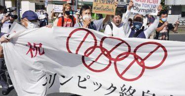 Demonstranten marschieren mit einem Banner und Plakaten bei einem Protest gegen die Olympischen und Paralympischen Sommerspiele. Foto: Koji Harada/Kyodo News/AP/dpa