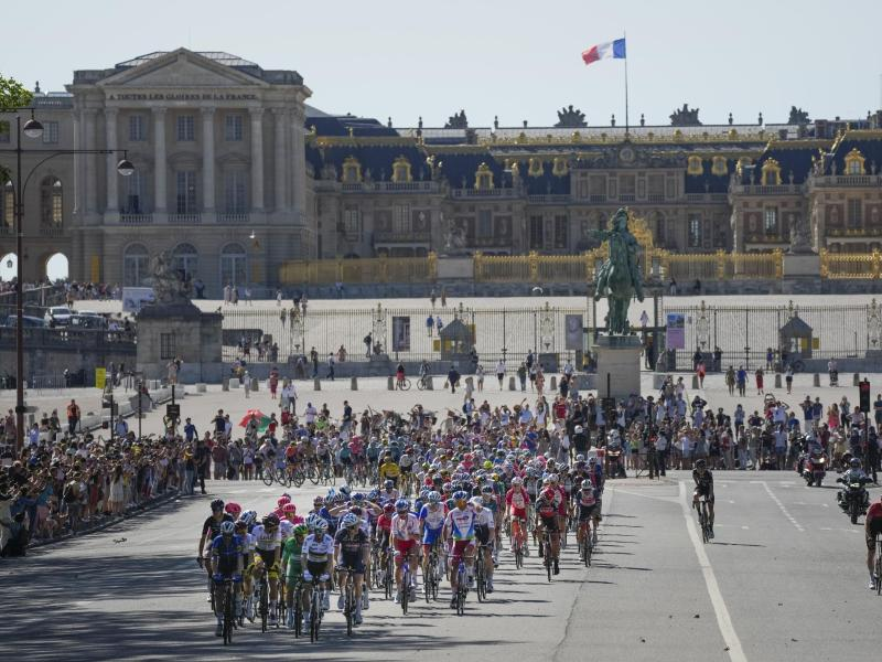 Endlich in Paris: Das Hauptfeld passiert das Schloss Versailles. Foto: Daniel Cole/AP/dpa
