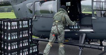 Ein Soldat entlädt am Nürburgring Kisten mit Trinkwasser aus einem Hubschrauber der Spezialkräfte vom Typ H145M. Foto: Luftwaffe/dpa