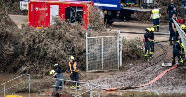 Helfer von Feuerwehr und Technischem Hilfswerk (THW) pumpen Wasser aus einem Regenrückhaltebecken ab, in dem sich noch Fahrzeuge befinden sollen. Foto: Marius Becker/dpa