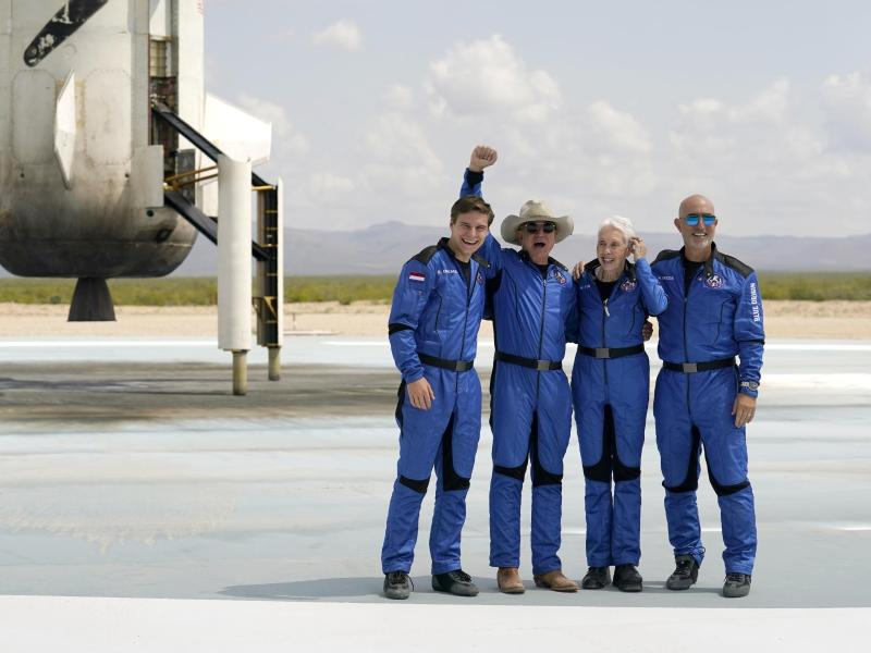 Oliver Daemen (l-r) aus den Niederlanden, Jeff Bezos, Gründer von Amazon und des Weltraumtourismus-Unternehmens Blue Origin, Wally Funk, ehemalige US-Pilotin, und Mark Bezos, Bruder von Jeff Bezos, stehen nach der Landung für ein Foto zusammen. Foto: Tony Gutierrez/AP/dpa