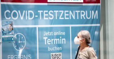 Eine Frau mit Maske läuft an einem Corona-Testzentrum am Berliner Alexanderplatz vorbei. Foto: Fabian Sommer/dpa