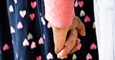 Eine Frau hält ein Mädchen an der Hand. Foto: Christian Charisius/dpa