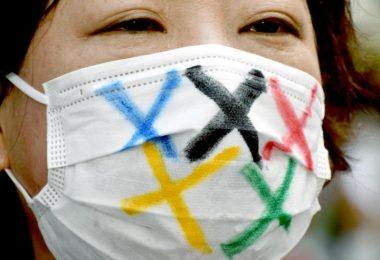 Eine Frau trägt einen Mund-Nasen-Schutz mit den fünf Farben der fünf olympischen Ringe während der Ankunft der olympischen Fackel in Tokio. Foto: Ramiro Agustin Vargas Tabares/ZUMA Press Wire/dpa