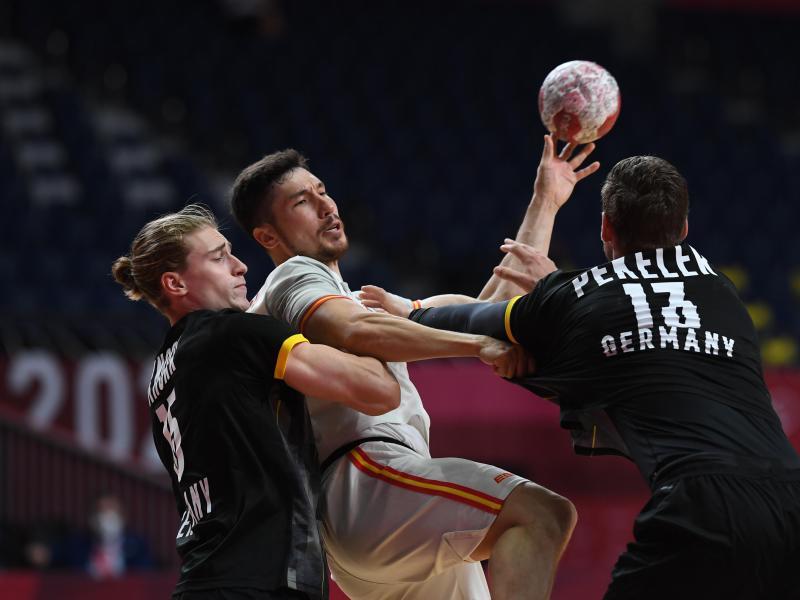Deutschlands Juri Knorr (l) und Hendrik Pekeler in Aktion mit Spaniens Alex Dujshebaev Dobichebaeva. Foto: Swen Pförtner/dpa