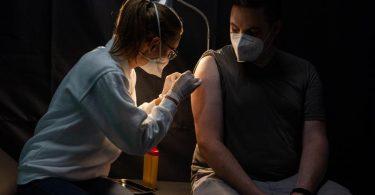 Eine Mitarbeiterin des Arbeiter-Samariter-Bundes (ASB) klebt nach einer Corona-Schutzimpfung ein Pflaster auf. (Archivbild). Foto: Nicolas Armer/dpa