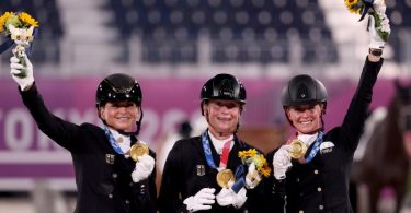 Dorothee Schneider (l-r), Isabell Werth und Jessica von Bredow-Werndl feiern ihr Team-Gold in der Dressur. Foto: Friso Gentsch/dpa
