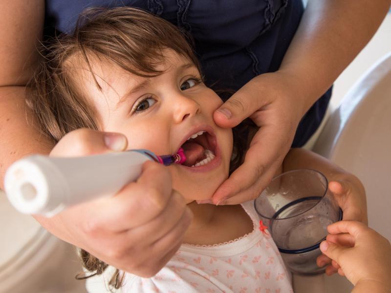 Bei Einjährigen sollte die fluoridhaltige Zahnpastamenge nicht größer als ein Reiskorn sein, ab dem Alter von zwei Jahren nicht größer als eine Erbse. Foto: Christin Klose/dpa-tmn