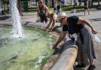 Menschen erfrischen sich bei Temperaturen über 40 Grad mit Wasser aus einem Brunnen auf dem Syntagma-Platz in Athen. Foto: Angelos Tzortzinis/dpa