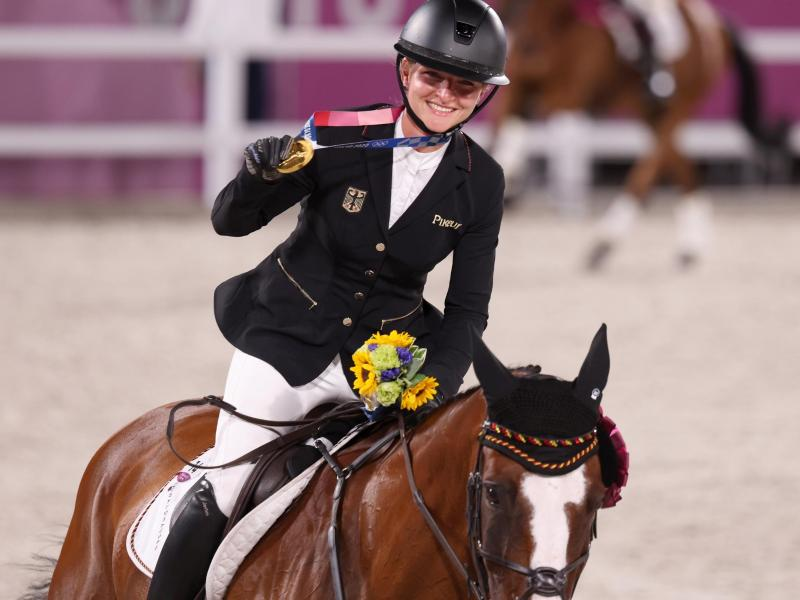Mit der Goldmedaille um den Hals reitet Julia Krajewski nach der Siegerehrung auf Amande de B`Neville eine Ehrenrunde. Foto: Friso Gentsch/dpa