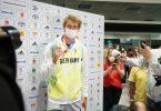 Tennisspieler Alexander Zverev zeigt nach seiner Ankunft aus Tokio auf dem Frankfurter Flughafen seine Medaille. Foto: Frank Rumpenhorst/dpa