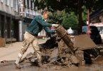 Ein Mann gießt nach der Hochwasserkatastrophe im nordrhein-westfälischen Gemünd Schlammreste auf einen Haufen von Schutt aus. Foto: Oliver Berg/dpa