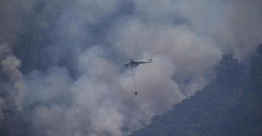 Ein Hubschrauber transportiert Löschwasser, um einen Waldbrand in der Türkei zu löschen. Foto: Emre Tazegul/AP/dpa