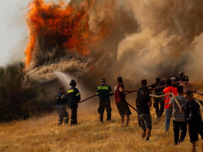 Feuerwehrleute und Freiwillige versuchen ein Feuer in Afidnes, etwa 30 Kilometer von der griechischen Hauptstadt Athen entfernt, zu löschen. Foto: Marios Lolos/XinHua/dpa