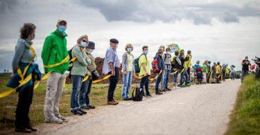 Umwelt- und Klimaschützer sowie Bewohner der angrenzenden Dörfer bilden am Rande des Braunkohletagebaus Garzweiler eine Menschenkette. Foto: Malte Krudewig/dpa