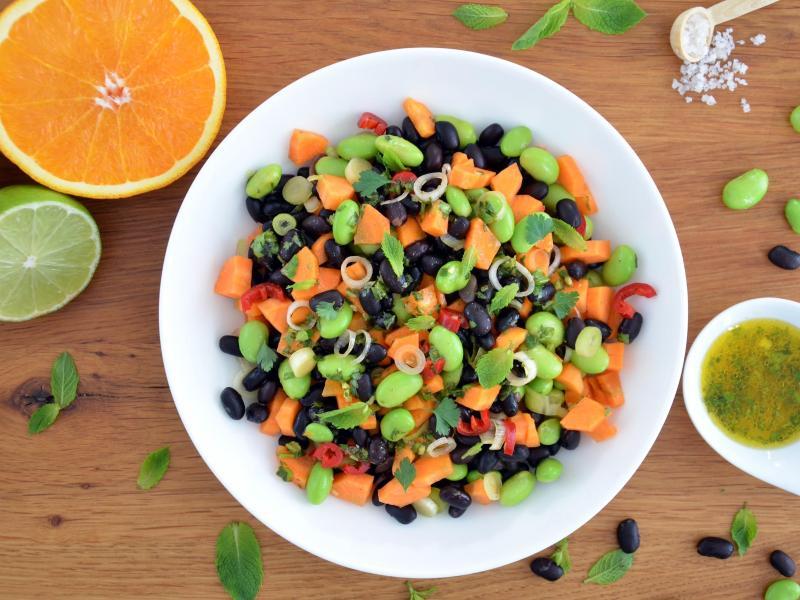 Leuchtend grüne Punkte vermischen sich mit dunklen und orangenen Farbtupfern: Zusammen mit dem Zitrusfrüchte-Dressing wird der nussig-würzige Bohnen-Mix zu einem frischen Salat. Foto: Julia Uehren/loeffelgenuss.de/dpa-tmn