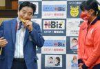 Nagoyas Bürgermeister Takashi Kawamura (l) biss in die Gold-Medaille von Miu Goto. Foto: Uncredited/Kyodo News/dpa
