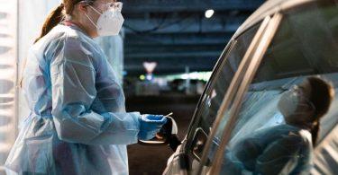 Eine Helferin testet Insassen eines Autos im «Testzentrum am Zoo» in Hannover. Foto: Julian Stratenschulte/dpa