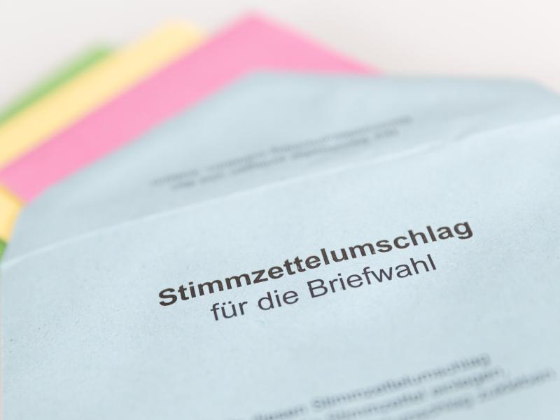 Verschiedene Stimmzettel stecken in einem Stimmzettelumschlag für die Briefwahl. Foto: Friso Gentsch/dpa