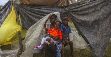 Kinder versuchen in Les Cayes, sich mit einer Plane vor dem Regen zu schützen. Foto: Joseph Odelyn/AP/dpa