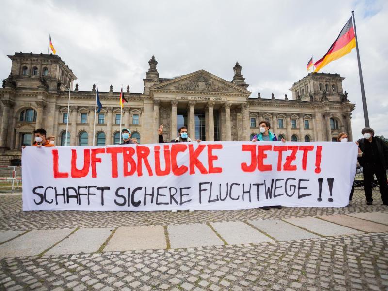 Demonstration für eine Luftbrücke aus Afghanistan vor dem Reichstagsgebäude in Berlin. Foto: Christoph Soeder/dpa