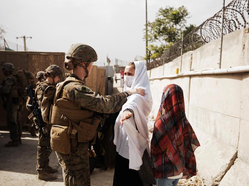 Zwei Zivilisten werden während einer Evakuierung am Hamid Karzai International Airport durch einen Kontrollpunkt geführt. Foto: Staff Sgt. Victor Mancilla/U.S. Marine Corps/AP/dpa