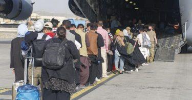 Menschen stehen auf dem Rollfeld und gehen an Bord eines US-Transportflugzeugs von Typ C-17 Globemaster III während ihrer Evakuierung am Hamid Karzai International Airport in Afghanistan. Foto: U.S. Marines/ZUMA Press Wire Service/dpa