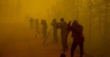 Freiwillige Helfer machen am Ort eines Waldbrands im Gebiet Gorny Ulus westlich von Jakutsk eine Pause. Das Ausmaß der verheerenden Waldbrände im Osten Russlands ist der Klimaexpertin Kirsten Thonicke zufolge «sehr beunruhigend». Foto: Ivan Nikiforov/AP/dpa