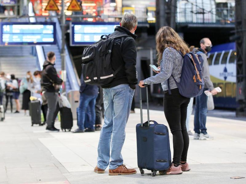 Reisende warten in Hamburg auf ihren Zug. Foto: Bodo Marks/dpa