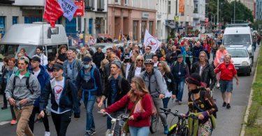 Aus Protest gegen die Corona-Politik wandern Demonstranten durch eine Straße. Neun Demonstrationen waren von der Polizei verboten worden. Foto: Christophe Gateau/dpa