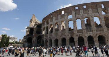 Touristen warten in einer Schlange, um das Kolosseum zu betreten. In Italien gelten ab diesem Mittwoch verschärfte Corona-Regeln. Foto: Riccardo De Luca/AP/dpa