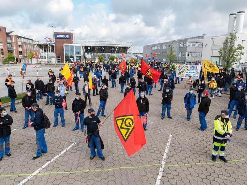 Beschäftigte des Airbus-Werkes in Hamburg-Finkenwerder demonstrieren im Mai 2021 vor den Toren des Werksgeländes. In dem seit Monaten schwelenden Konflikt um den geplanten Konzernumbau sollen nun Verhandlungen zwischen der IG Metall und dem Flugzeugbauer beginnen. Foto: Daniel Reinhardt/dpa