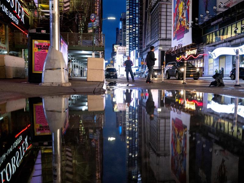 Die Lichter des Times Square spiegeln sich im Wasser. Foto: Craig Ruttle/AP/dpa