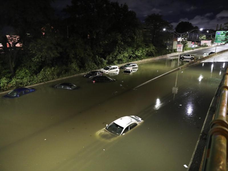 Fahrzeuge stehen im Hochwasser auf einer Straße New Yorks. Foto: Wang Ying/XinHua/dpa