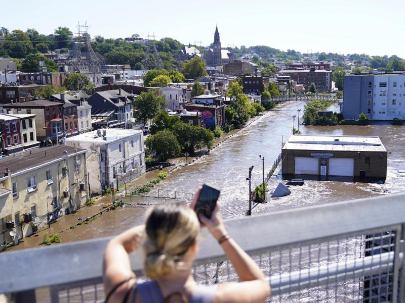 Eine Frau fotografiert das Hochwasser in Philadelphia. Foto: Matt Rourke/AP/dpa