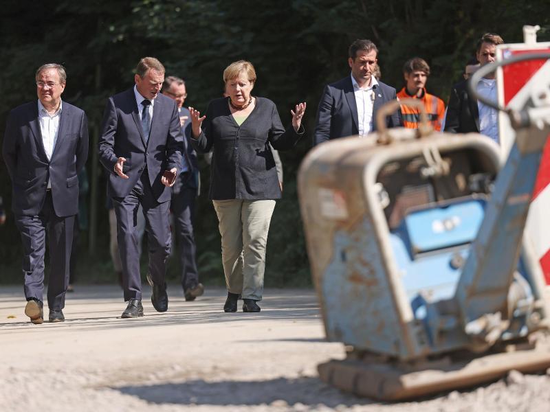 Angela Merkel und Armin Laschet begutachten eine neugebaute Brücke in Hagen. Die Bundeskanzlerin hat erneut die Flutgebiete in Nordrhein-Westfalen besucht. Foto: Oliver Berg/dpa Pool/dpa
