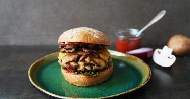 Krosse Burger aus braunen Champignons und Dinkel-Bulgur liegen zusammen mit Cheddar und roten Zwiebelringen zwischen zwei Brötchenhälften. Foto: Manfred Zimmer/herrgruenkocht.de/dpa-tmn