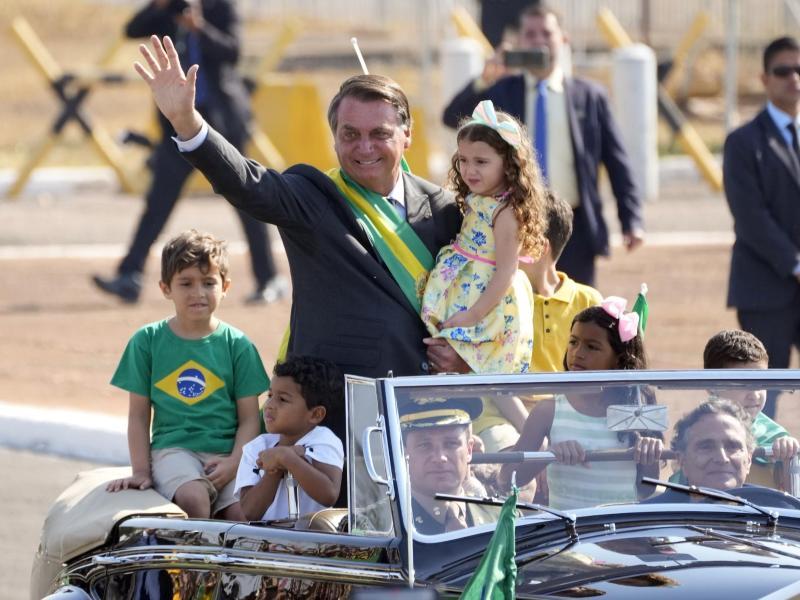 Jair Bolsonaro (M) kommt zu einer Flaggenhissungszeremonie in der Präsidentenresidenz. Foto: Eraldo Peres/AP/dpa