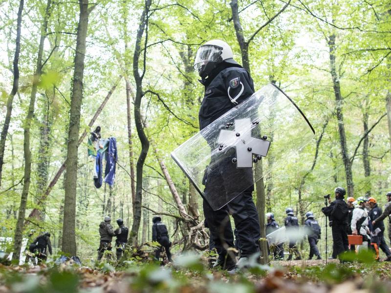 Polizisten stehen im September 2018 vor einer Barrikade im Hambacher Forst, in der sich eine Aktivistin festgebunden hat. Foto: Marcel Kusch/dpa