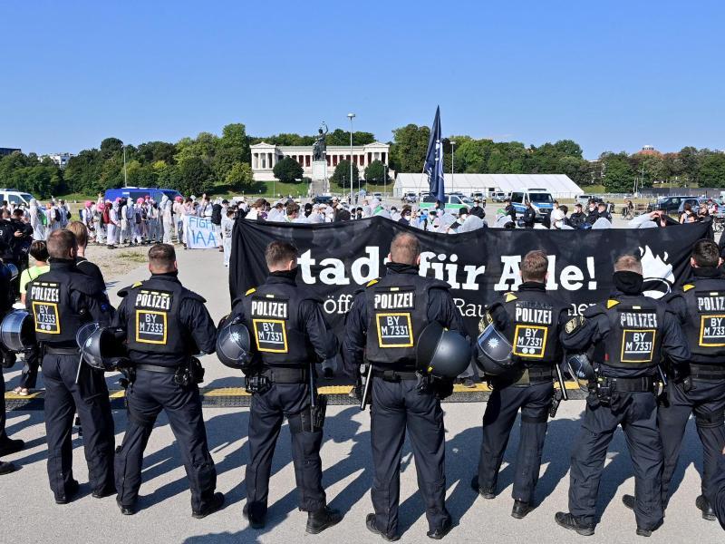 Polizisten umstellen auf der Theresienwiese einen Demonstrationszug. Foto: Peter Kneffel/dpa