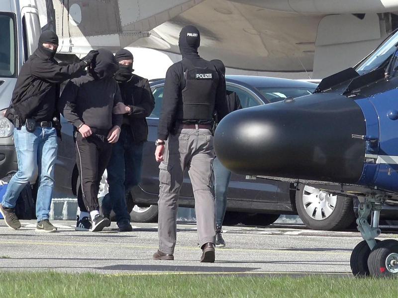Ein mutmaßliches Mitglied der Terrormiliz IS wird auf dem Flughafen Hamburg zu einem Hubschrauber der Bundespolizei gebracht. Foto: Bodo Marks/dpa