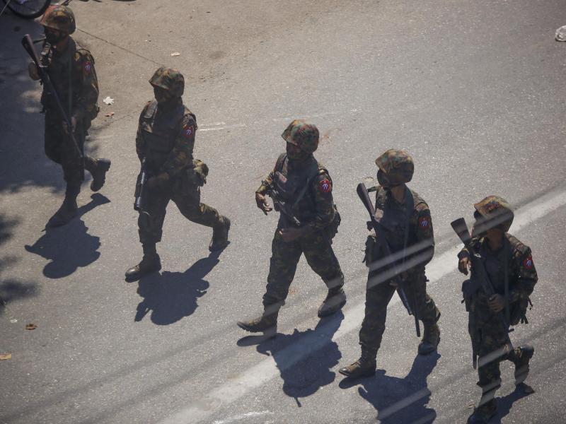Soldaten gehen im März während eines Protestes gegen den Militärputsch in Myanmar über eine Straße. Symbolbild. Foto: Str/AP/dpa